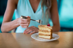 Woman eating dessert in cafe. Mid-section of woman sitting in cafe and eating dessert Stock Images
