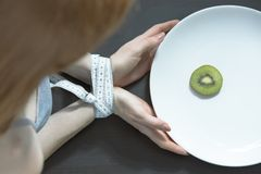 Woman with an eating disorder. And her hands bound by tape-measure limiting her dinner to a kiwi Royalty Free Stock Images