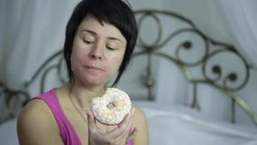 Woman eating a donut on a bed, breakfast with junk food.  stock video