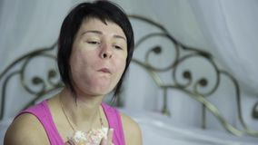 Woman eating a donut on a bed, breakfast with junk food.  stock footage