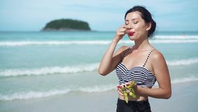 Woman eating dragon fruit with a spoon on a beach stock video