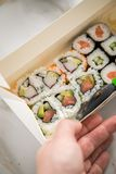 Woman eating edamame, salmon, surimi, cucumber and avocado Maki and inside out California sushi with soy sauce, pickled ginger, stock images