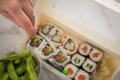 Woman eating edamame, salmon, surimi, cucumber and avocado Maki and inside out California sushi with soy sauce, pickled ginger,. Wasabi and soy sauce in take stock photography