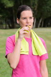 Woman Eating Energy Bar. Young athlete woman outdoors, with sport wear and towel eating an energy bar Royalty Free Stock Photography