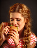 Woman eating fast food . Girl enjoying delicious hamburger. Stock Images