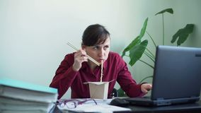 Woman Eating Fast Food while Working in Office stock video