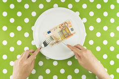 Woman eating fifty euroes banknotel for dinner Stock Photo