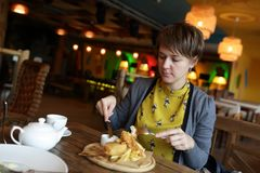 Woman eating fillet of cod Royalty Free Stock Photos