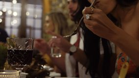 Dinner party. Woman eating food with friends sitting at dinner table. Dinner party with people having food and drinks stock video footage