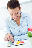 Woman eating french cookies at home. Beautiful woman eating french cookies at home Royalty Free Stock Photos