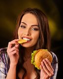 Woman eating french fries and hamburger on table. Royalty Free Stock Images