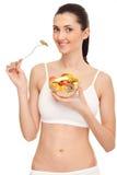 Woman eating fresh fruit salad. Fit woman eating fresh fruit salad, isolated on white background Royalty Free Stock Photo
