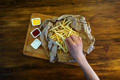 Woman eating fries with sauce in cafe, top view photo. Girl eating fries with sauce in cafe, top view photo Royalty Free Stock Images