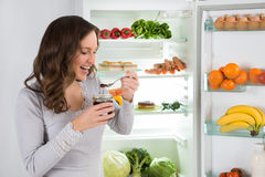 Woman Eating In Front Of Fridge. Young Woman Eating In Front Of Fridge In Kitchen royalty free stock photo