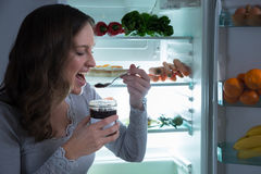 Woman Eating In Front Of Fridge Stock Photos