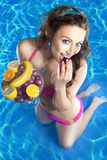 Woman eating fruit in pool Royalty Free Stock Image