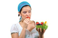 Woman eating fruits. Young woman with bandanna eating a strawberry from fruit bowl Royalty Free Stock Image