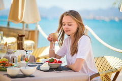 Woman eating fruits in a beach restaurant Royalty Free Stock Photo