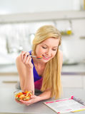 Woman eating fruits salad in kitchen Stock Image