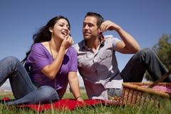 Woman eating grape man watching Stock Images