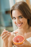 Woman eating grapefruit stock images