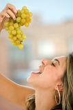 Woman eating grapes Stock Photos