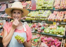 Woman eating grapes against blurry grocery aisle royalty free stock photos