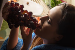 Woman eating grapes Stock Image
