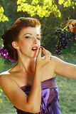 Woman eating grapes outdoors in the park Royalty Free Stock Image