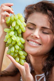 Woman eating grapes in wheat field. Picnic. Stock Photo