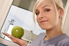 Woman eating a green apple. Blond, young girl, woman eating a green apple Stock Photo