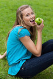 Woman eating a green apple while sitting in a park Stock Image