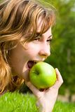 Woman eating green apple on the summer glade Royalty Free Stock Photography