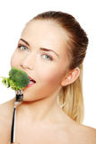 Woman eating green broccoli Royalty Free Stock Photo