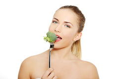 Woman eating green broccoli stock photography