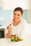 Woman eating green salad Stock Photos