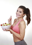 Woman eating green salad and strawberry Stock Photography