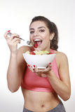 Woman eating green salad and strawberry Stock Photos