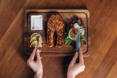 Woman eating grilled salmon steak served on wooden board with lemon and lettuce stock photo
