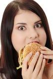 Woman eating hamburger Stock Photos