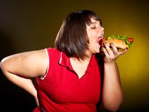 Woman eating hamburger. Stock Photos