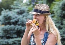 Woman eating a hamburger Stock Photos