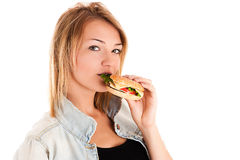 Woman eating a hamburger Stock Images