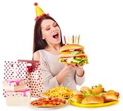 Woman eating hamburger at birthday. Royalty Free Stock Photography