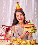 Woman eating hamburger at birthday Royalty Free Stock Photo