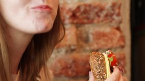 Woman eating a hamburger in a cafe stock footage