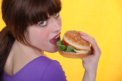 Woman eating hamburger Stock Photo