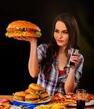 Woman eating hamburger. Girl bite of very big burger stock photos