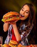 Woman eating hamburger. Girl bite of very big burger royalty free stock images