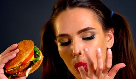 Woman eating hamburger. Girl wants to eat fast food. Woman eating hamburger. Girl wants to eat burger. How quickly to cook dinner. Portrait of person with good royalty free stock images